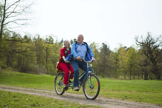 Stock Photo: 4306R-26109 Senior couple riding on tandem bicycle