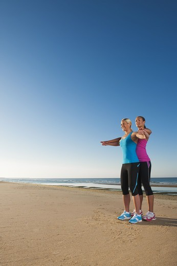 Two women exercising together on beach : Stock Photo