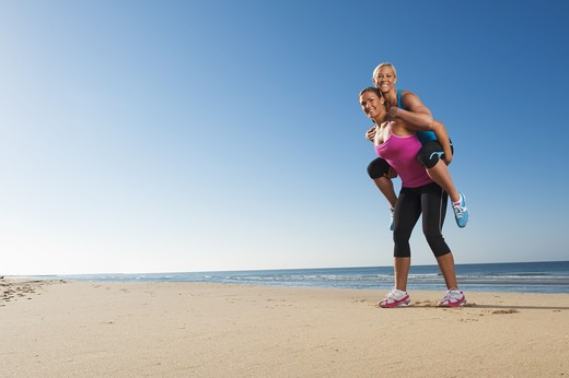 Stock Photo: 4306R-26363 Woman giving friend piggy back on beach