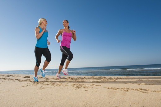 Stock Photo: 4306R-26369 Two women jogging on beach