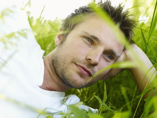 Stock Photo: 4306R-26467 Young man lying on grass and looking away