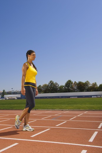 Female athlete standing at stadium : Stock Photo