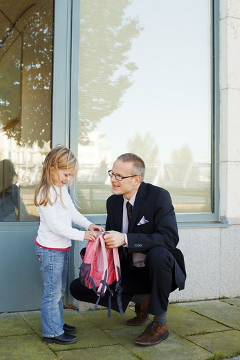 Stock Photo: 4306R-27392 Father helping daughter with backpack