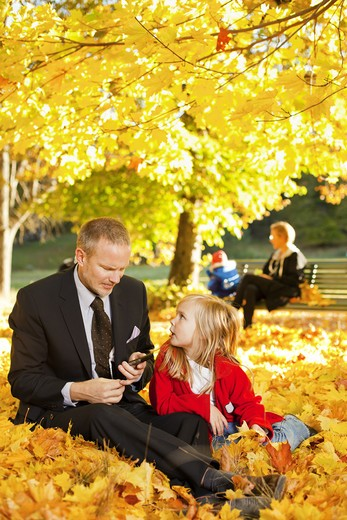 Father and daughter sitting in autumn leaves in park : Stock Photo