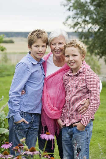 Stock Photo: 4306R-27500 Grandmother with grandsons in garden