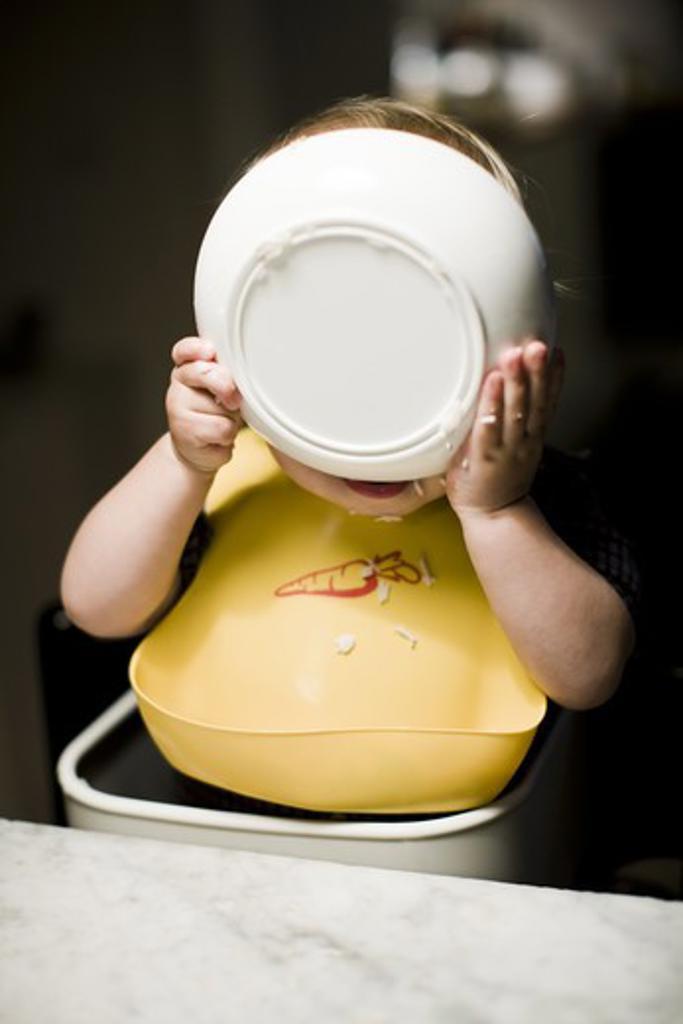 Boy wearing bib eating from bowl : Stock Photo