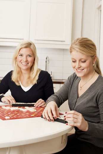 Stock Photo: 4306R-27580 Two young women playing board game in kitchen