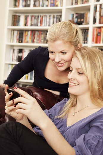 Two women looking at cell phone : Stock Photo