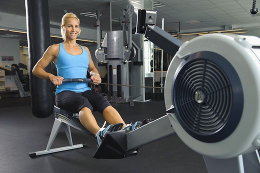 Woman exercising at oarsman in gym : Stock Photo