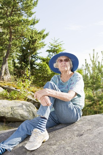 Portrait of senior woman sitting on rock : Stock Photo