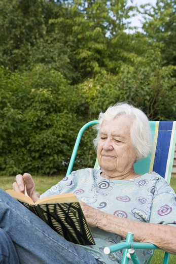 Stock Photo: 4306R-27830 Portrait of senior woman reading book in backyard