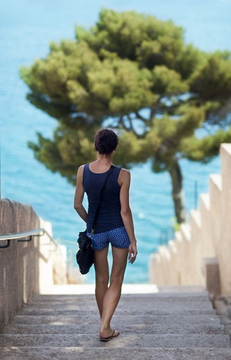 Stock Photo: 4306R-28285 Woman walking down stairs into sea