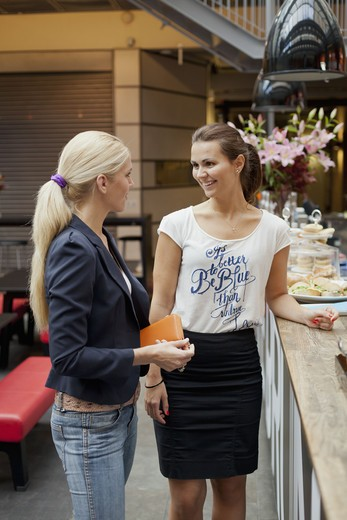 Portrait of young women laughing in cafe : Stock Photo