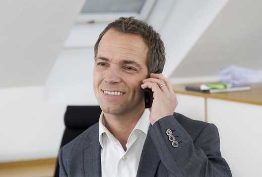 Stock Photo: 4306R-28503 Smiling businessman talking via cell phone