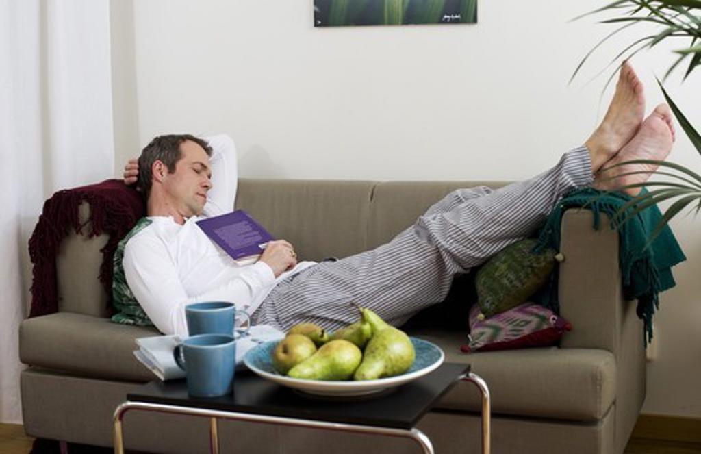 Stock Photo: 4306R-28524 Mid adult man lying on sofa and sleeping