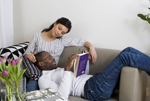 Stock Photo: 4306R-28526 Couple on sofa, man reading book