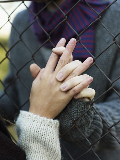 Young couple holding hands through wire fence : Stock Photo