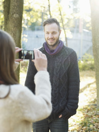 Stock Photo: 4306R-28581 Woman photographing young man by tree