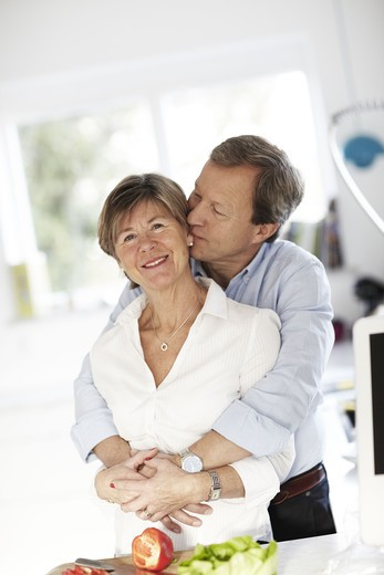 Stock Photo: 4306R-28796 Portrait of mature couple embracing in kitchen