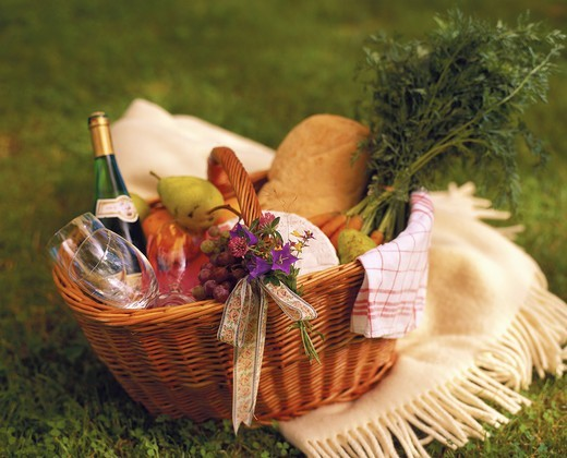Stock Photo: 4306R-6247 Picnic basket containing wine bottle, fruit and glasses on blanket