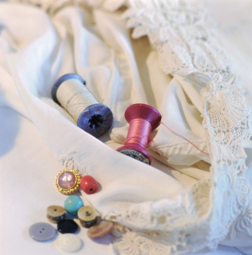 Stock Photo: 4306R-6530 Two thread rolls with variety of buttons on cloth
