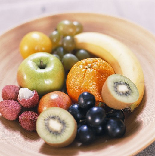 Stock Photo: 4306R-6695 Variety of fruits including kiwi, grapes, litchi, orange, apple and banana on plate