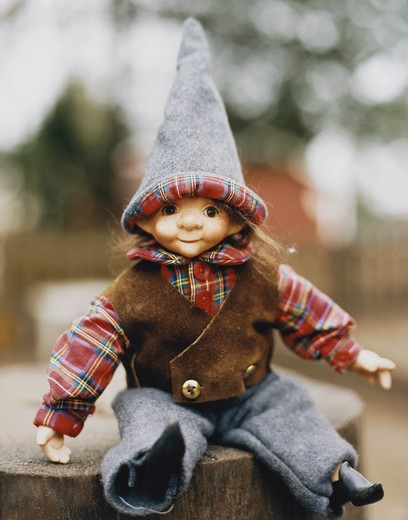 Stock Photo: 4306R-7007 Doll wearing hat and waistcoat on tree trunk