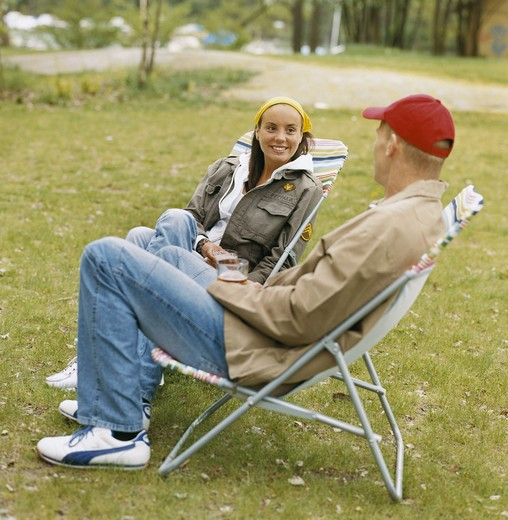 Stock Photo: 4306R-7609 Couple sitting on outdoor chairs in park