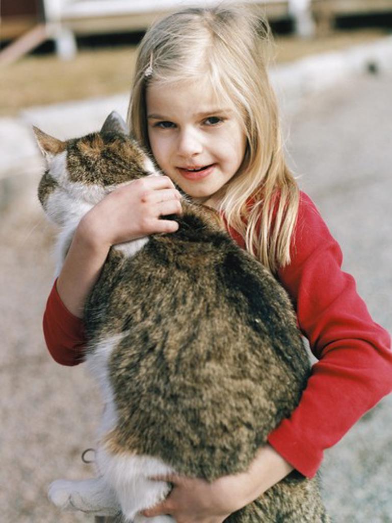 Stock Photo: 4306R-7701 Blonde girl carrying pet cat