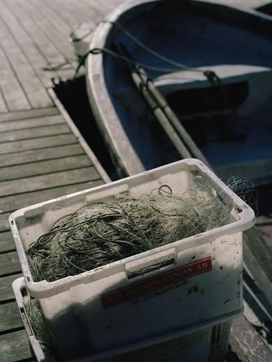 Stock Photo: 4306R-7957 Fishing net kept in box on wooden jetty next to boat