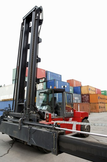 Red forklift truck with pile of big metal goods containers : Stock Photo