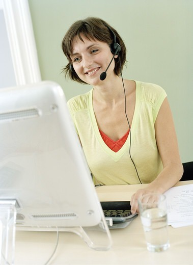 Stock Photo: 4306R-8459 Smiling woman wearing headphones sitting in front of computer