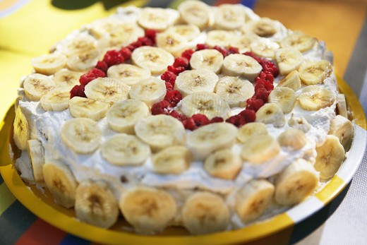 A cake with banana slices and ?10? written with berries. : Stock Photo