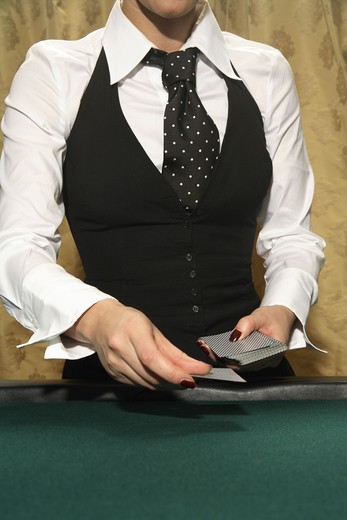 Stock Photo: 4306R-9011 A female croupier handing out cards.