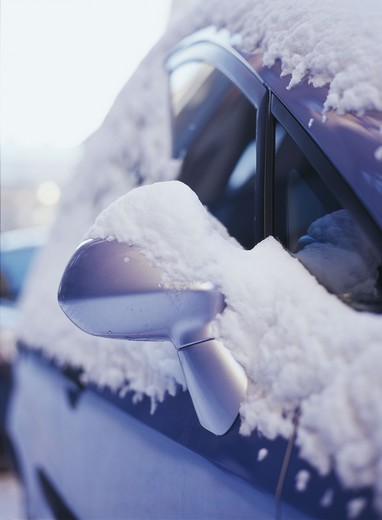 A mirror on a car covered in snow. : Stock Photo