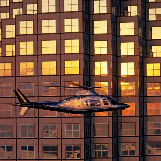 A Corporate Helicopter Lands Near a Skyscraper : Stock Photo