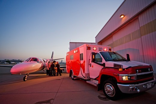 An Airplane and Ambulance Providing Medical Transport : Stock Photo