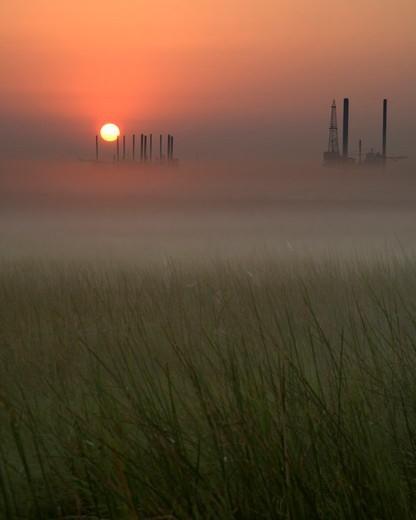 Oil Rigs Across a Marsh at Sunrise : Stock Photo