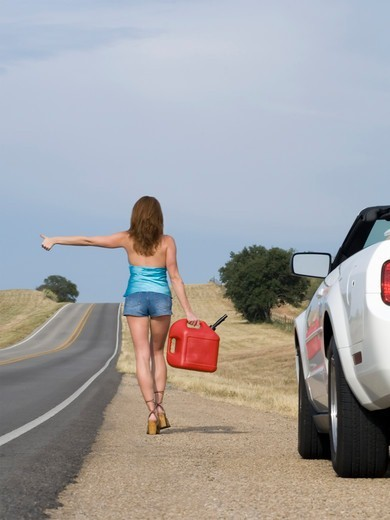 Hitchhiker Begins a Long Walk to the Gas Station : Stock Photo
