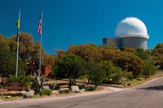 Stock Photo: 4313-1180 The 2.1-meter Telescope is seen near the flagpoles and sign marking Kitt Peak National Observatory, Arizona.