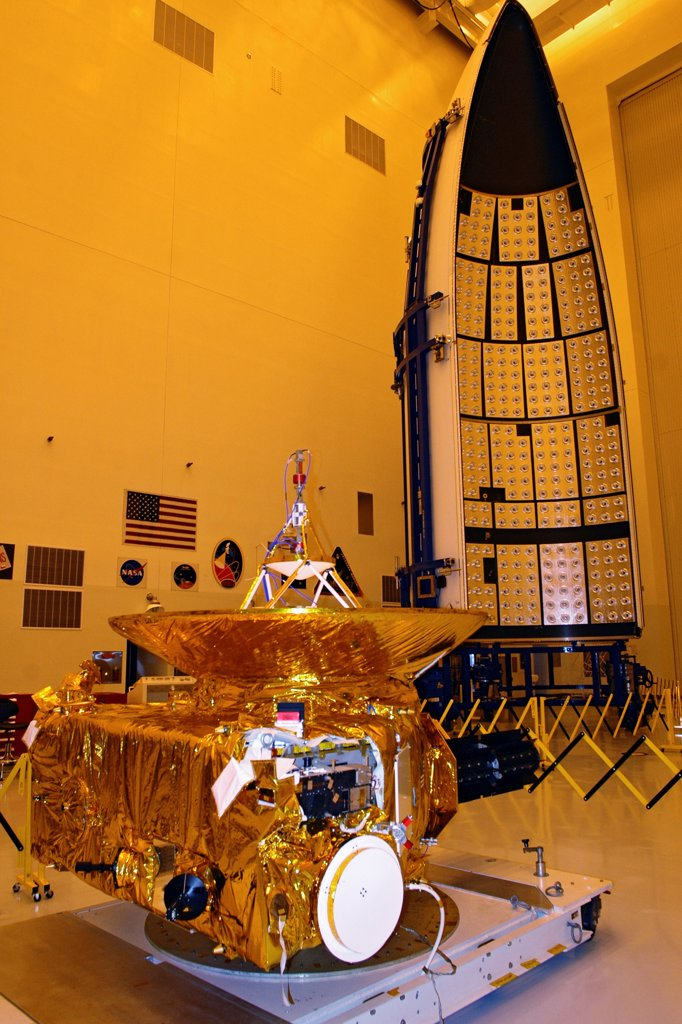 NASA's nuclear-powered New Horizons spacecraft, the world's first mission to Pluto, is prepared for launch inside a cleanroom at the Kennedy Space Center. The payload fairing for the Atlas V rocket that will launch it can be seen in the background. : Stock Photo