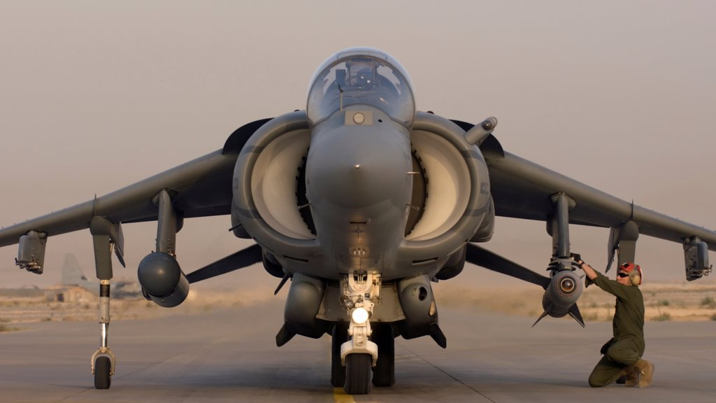 A Ground Crewman Arms Weapons on a US Marine Corps AV-8B Harrier at Al Asad Air Base in the Al Anbar Province of Iraq : Stock Photo