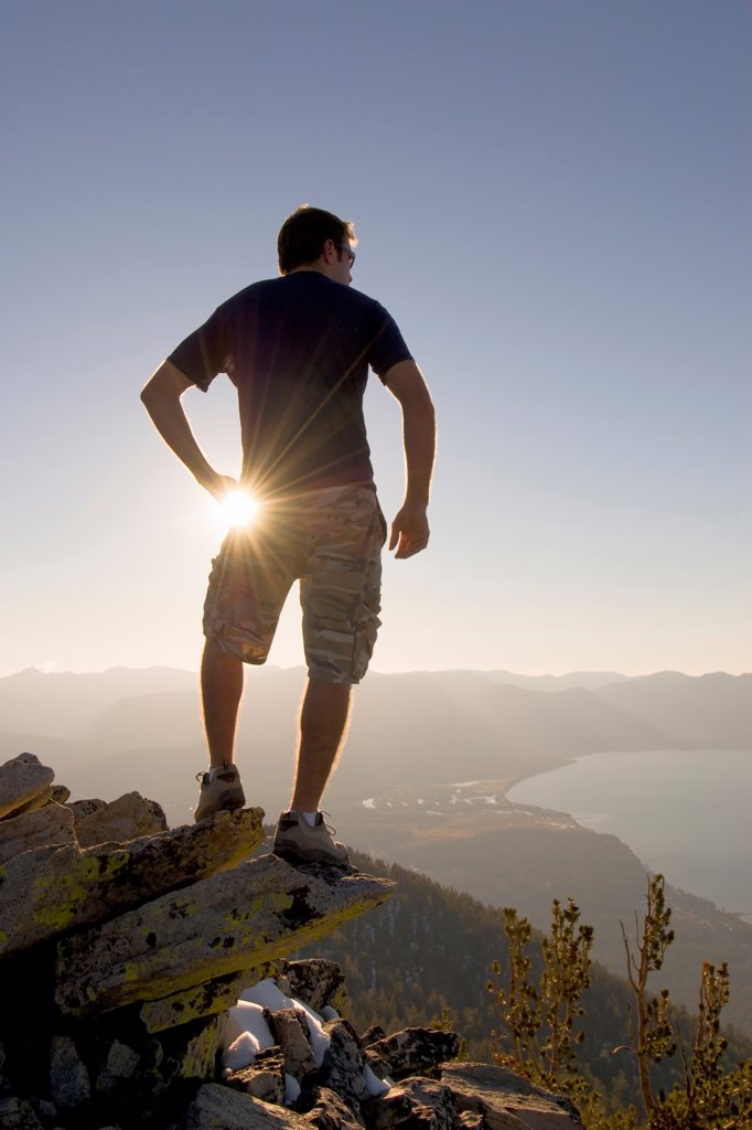 A Hiker Gazes Across Lake Tahoe at Sunset From a Mountaintop : Stock Photo