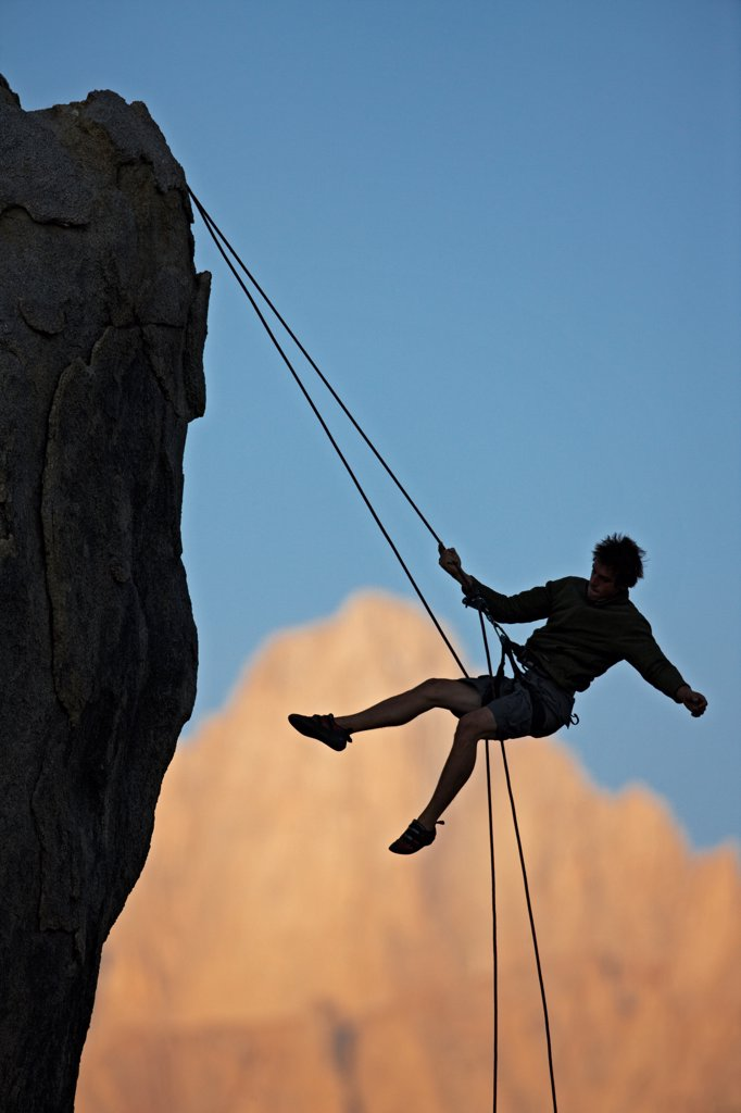 A climber swings out while rappelling off of a cliff , silhouetted against Mount Whitney in California's eastern high Sierra Nevada mountains. The climber is in the Alabama Hills, near the town of Lone Pine. : Stock Photo
