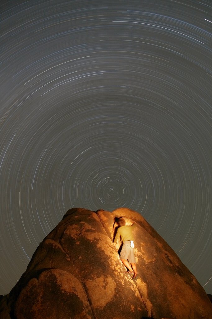 A climber ascends a boulder in the Alabama Hills of California, near the town of Lone Pine, into a 'vortex' of stars. The center star is Polaris, The North Star, and the star trail circles result from the rotation of the Earth. : Stock Photo