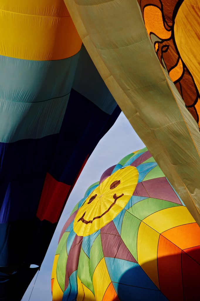 Stock Photo: 4316-2508 A smiling face on the top of an inflating balloon seems to peep through two other inflating balloons at the Reno Balloon Races, Reno, Nevada.