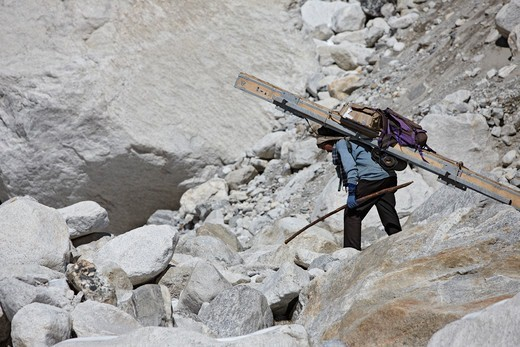 A Nepalese porter hunches over under the weight of an extremely heavy load as he ascends slopes under Mount Everest. : Stock Photo