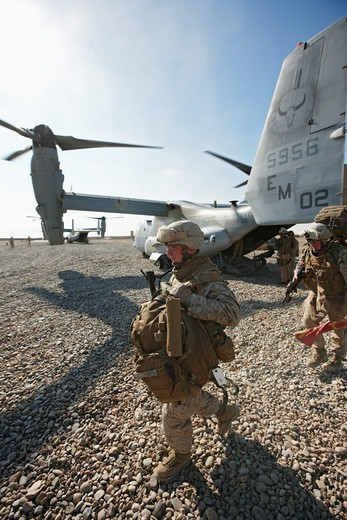 A U.S. Marine offloads gear from an MV-22 Osprey after landing at a combat outpost in the Helmand Province of southern Afghanistan. : Stock Photo