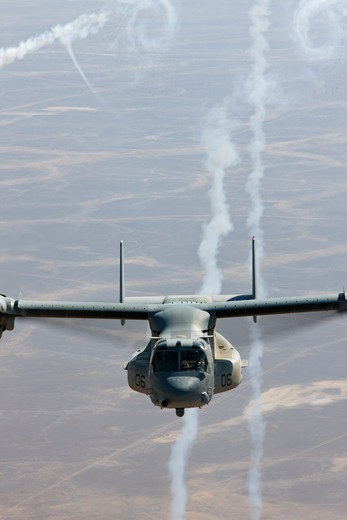 A U.S. Marine Corps MV-22 Osprey expends flares during a combat operation over the Helmand Province of southern Afghanistan. : Stock Photo