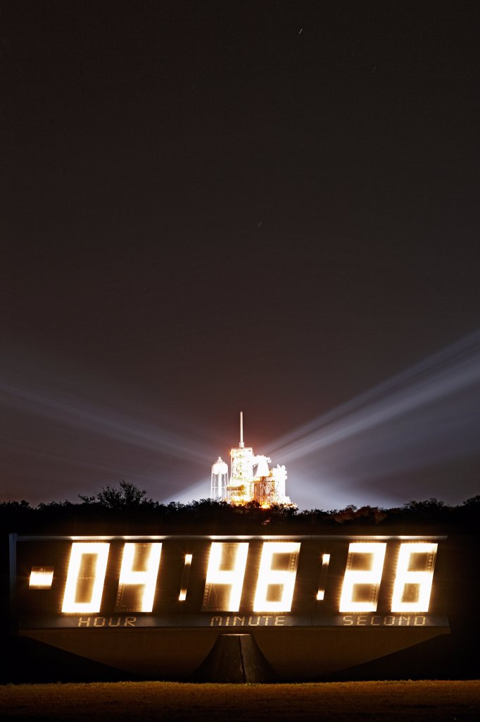 Stock Photo: 4316-2907 The space shuttle Endeavour, prepared for launch on pad 39A, glows behind a sign counting down the hours until liftoff.